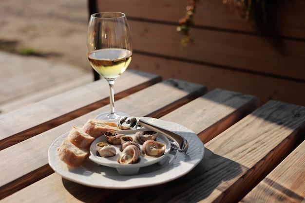 다양한 소스, 페스토, 트러플, 치즈, 프렌치 바게트 조각, 껍질용 포크, 야외 카페의 나무 테이블과 함께 흰색 클래식 접시에 제공되는 와인과 달팽이 껍질이 있는 접시.
