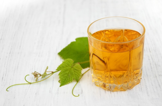 Glass with wine and white grape leaves