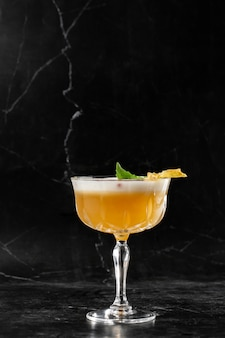Glass with yellow lemon cocktail decorated with dried pineapple and mint on the bar on a black