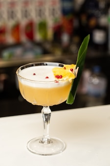 Glass with yellow lemon cocktail decorated with dried pineapple and mint on the blurred bar