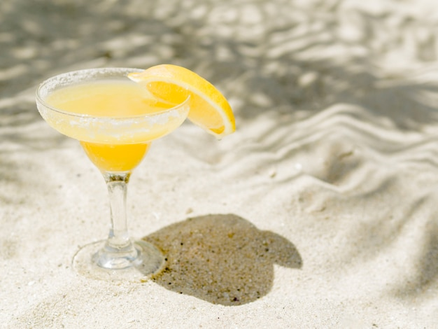 Glass of yellow cocktail with lemon slice placed on sand