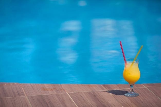 Glass of yellow juice with ice against the wall of the pool in summer