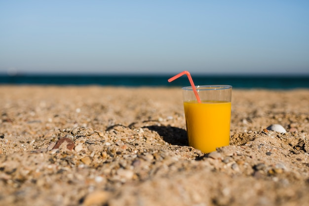 A glass of yellow juice with red drinking straw in sand at beach