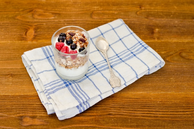Glass of yogurt with granola and berries on a wooden table. traditional american breakfast