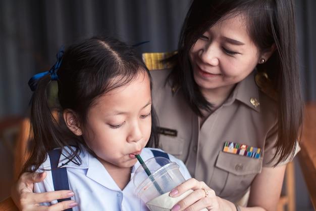 アジアの娘は、彼女の母親と一緒にglassaからチューブでジュースを飲みます。