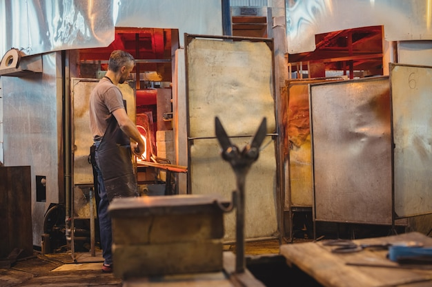 Soffiatore di vetro che riscalda un bicchiere nel forno di soffiatori di vetro