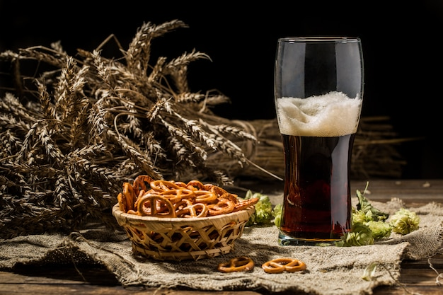 Glasse beer with wheat and hops, basket of pretzels