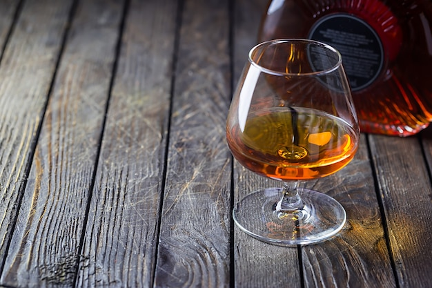 Glasse of brandy or cognac and bottle on dark.