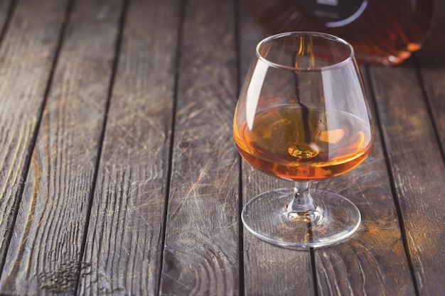 브랜디 또는 코냑의 glasse와 어두운 병.