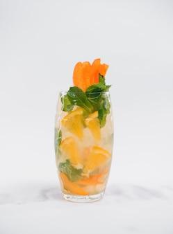 Стакан напитка с кубиками льда и фруктами, изолированные