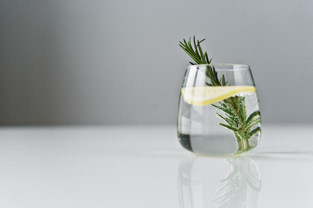 レモン、ローズマリーと純粋な水のガラス。 Premium写真