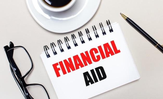 眼鏡、白い一杯のコーヒー、financial aidという言葉が書かれた白いノート、ボールペンが明るい背景に横たわっています。フラットレイ。上からの眺め。