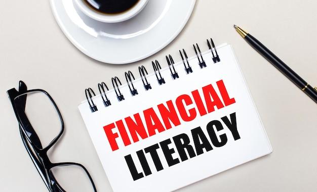 Очки, белая чашка кофе, белый блокнот с надписью «финансовая грамотность» и шариковая ручка лежат на светлом фоне. плоская планировка. вид сверху.