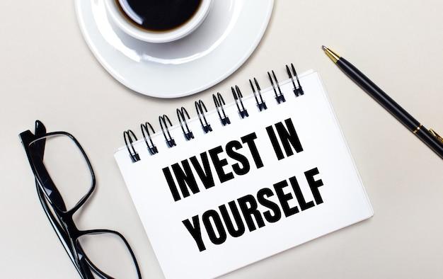 밝은 배경에 안경, 흰색 컵의 커피, invest in yourself라는 단어가있는 흰색 노트북과 볼펜이 놓여 있습니다. 평평하다. 위에서 봅니다.