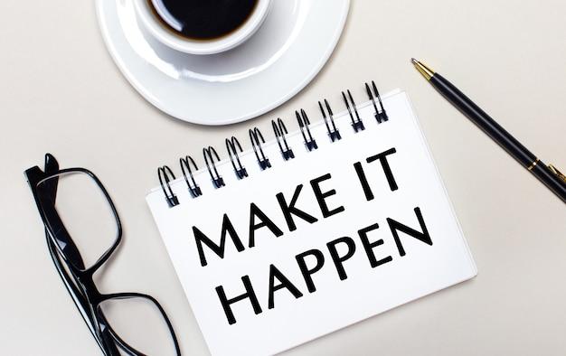 안경, 흰색 컵의 커피, make it happen이라는 단어가 적힌 흰색 노트북과 볼펜이 밝은 표면에 놓여 있습니다. 평평하다. 위에서보기