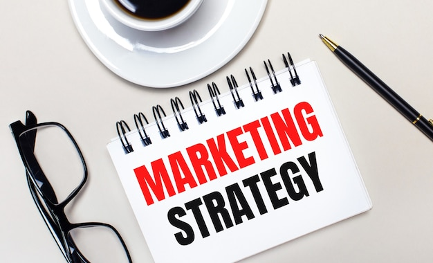 Очки, белая чашка кофе, белый блокнот с надписью «маркетинговая стратегия» и шариковая ручка лежат на светлом фоне. плоская планировка. вид сверху.