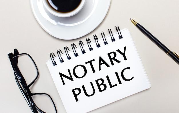 眼鏡、白い一杯のコーヒー、notary publicという言葉が書かれた白いノート、ボールペンが明るい面に置かれています。フラットレイ。上からの眺め。