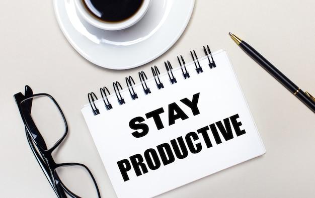 メガネ、白い一杯のコーヒー、stay productiveという言葉が書かれた白いノート、ボールペンが明るい背景に横たわっています。