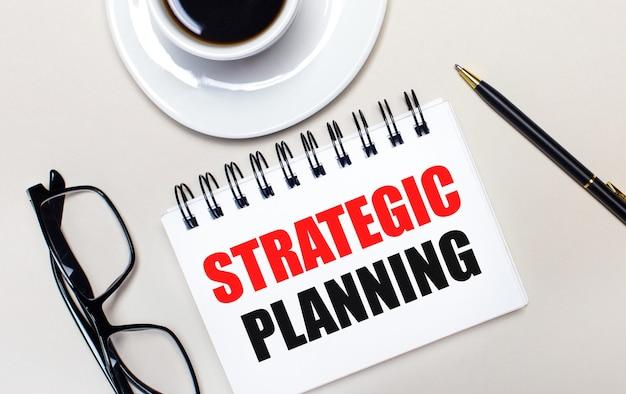 メガネ、白い一杯のコーヒー、戦略的計画という言葉が書かれた白いノート、ボールペンが明るい背景に横たわっています。フラットレイ。上からの眺め。