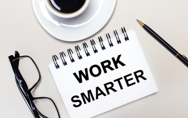 밝은 배경에 안경, 흰색 컵의 커피, work smarter라는 단어가있는 흰색 노트북 및 볼펜이 놓여 있습니다.