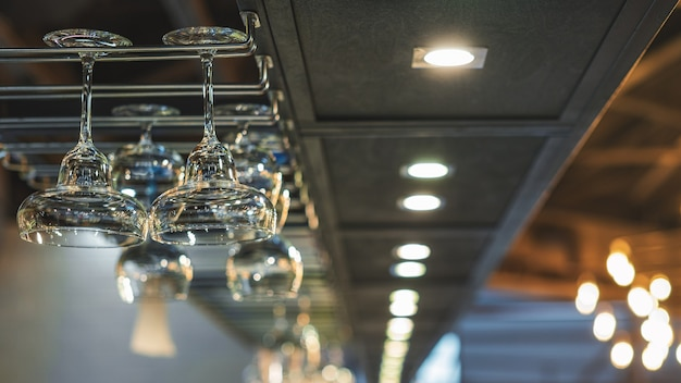 Glasses for alcoholic beverages are suspended above the bar selective focus