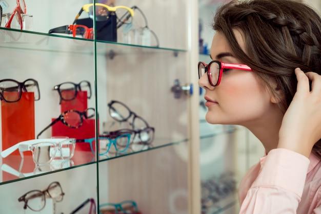 Очки всегда мало. боковой портрет красивой современной женщины в прозрачных очках смотрит на подставку с очками и выбирает из множества оправ, желая купить что-то новое