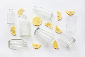 Glasses and bottle for drinks with lemon slices. Healthy vitamin drink.