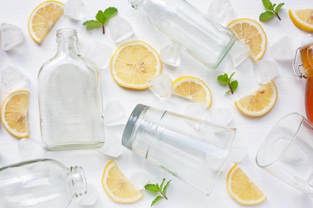 Очки и бутылка для напитков с ломтиками лимона, мятой и медом Premium Фотографии