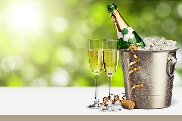 Бокалы и бутылка шампанского в холодильнике на естественном фоне