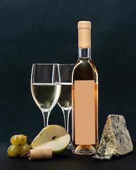 Бокалы и бутылка белого вина с сыром с голубой плесенью и фруктами