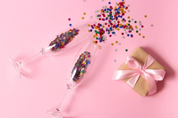 Очки и конфетти на цветном фоне вид сверху