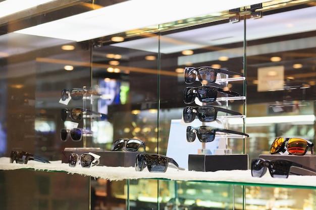 Очки и очки показывают в витрине витрины оптического магазина роскошной розничной торговли
