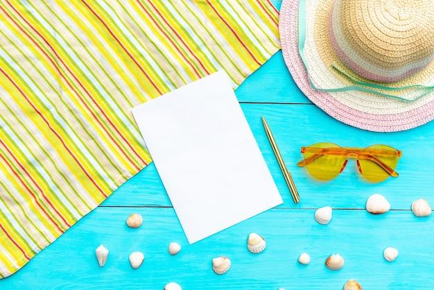 안경 및 파란색 배경에 여름 휴가를위한 모자. 쉘과 여름 액세서리로 둘러싸인 메모장과 볼펜. 평면도. 공간을 복사하십시오.