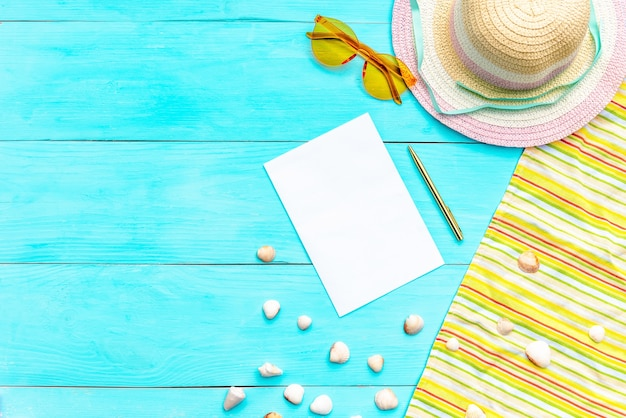 青い表面の夏休みのためのメガネと帽子