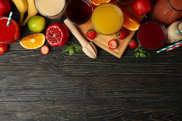 Стаканы и банки с разными соками на деревянных