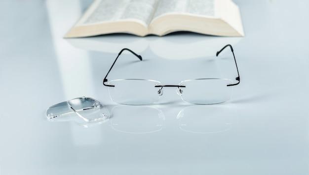 Очки и линзы на зеркальном столе, открытая книга. концепция видения.