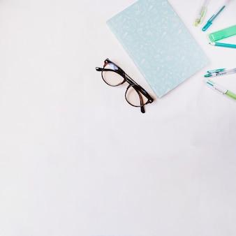Очки и ноутбук рядом с пишущими принадлежностями