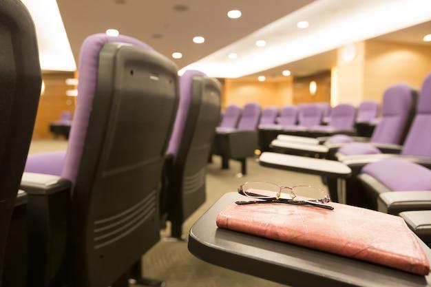 Очки и тетради в конференц-зале