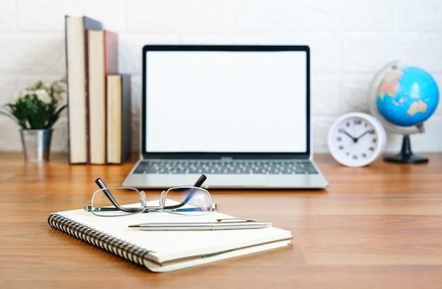 デッキ上の空白の画面のラップトップコンピューターを備えたメガネとメモ帳ラップトップを備えた職場o
