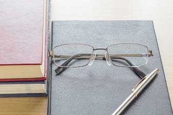 Очки и ручку положить на блокнот