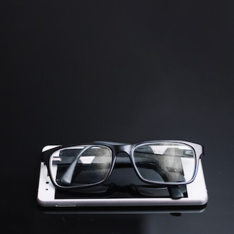 Glasses and phone on black table