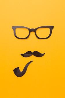 メガネと黄色の背景上のパイプ