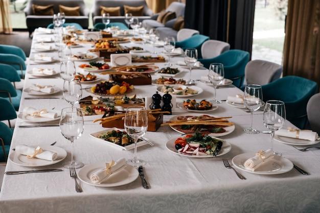 축하를 위해 레스토랑의 긴 테이블에 있는 안경과 접시