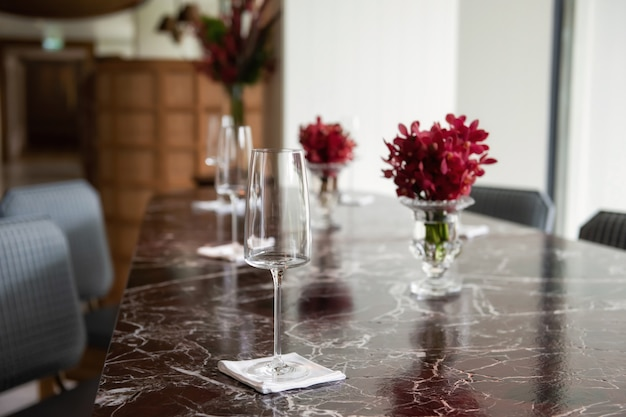 テーブルの上のグラスと赤い花