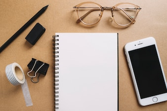 Glasses and smartphone near office supplies