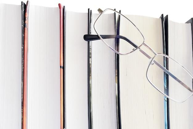 白い背景の上のメガネと厚い本。教育の概念。