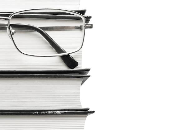 Очки и толстые книги на белой стене. концепция образования.