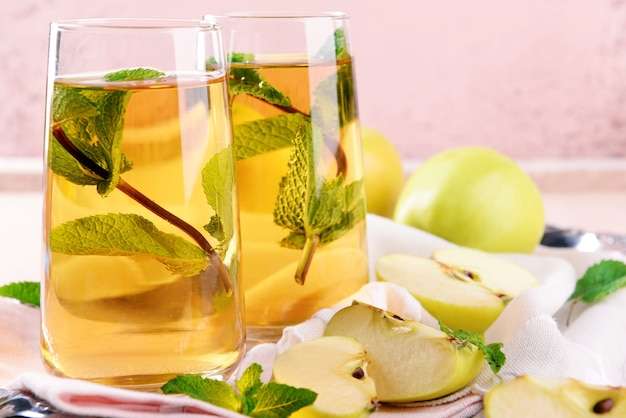 Glasses of apple juice with fruits and fresh mint on table