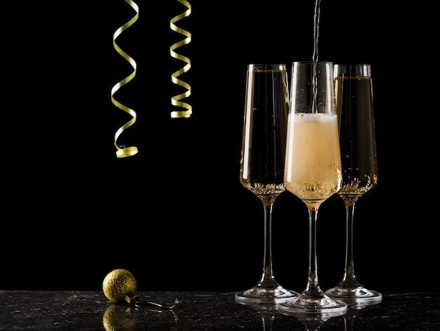 Бокалы наполнены игристым вином на черном фоне с висящим серпантином.