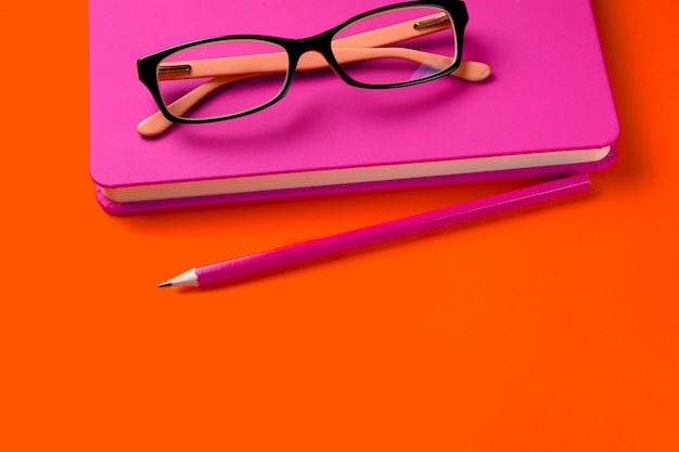 The glasses are lying on a pink notebook, next to a pencil, against a background of lush lava. workplace freelancer, businessman, entrepreneur.